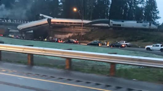 An Amtrak train derailment hangs over an overpass along I-5 south of Seattle on Dec 18th 2017