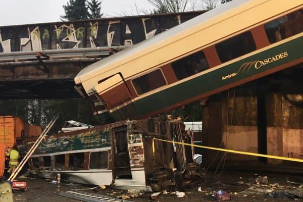 An Amtrak train derailment hangs over an overpass along I-5 south of Seattle on Dec 18th, 2017.