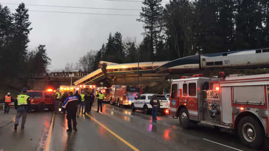 An Amtrak train derailment hangs over an overpass along I-5 south of Seattle on Dec 18th, 2017.