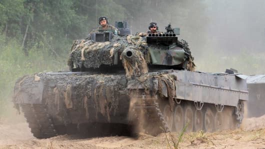 Soldiers serving in the NATO enhanced Forward Presence (eFP) battalion battle group ride a tank as they take part in an exercise in Rukla, Lithuania, on August 11, 2017.