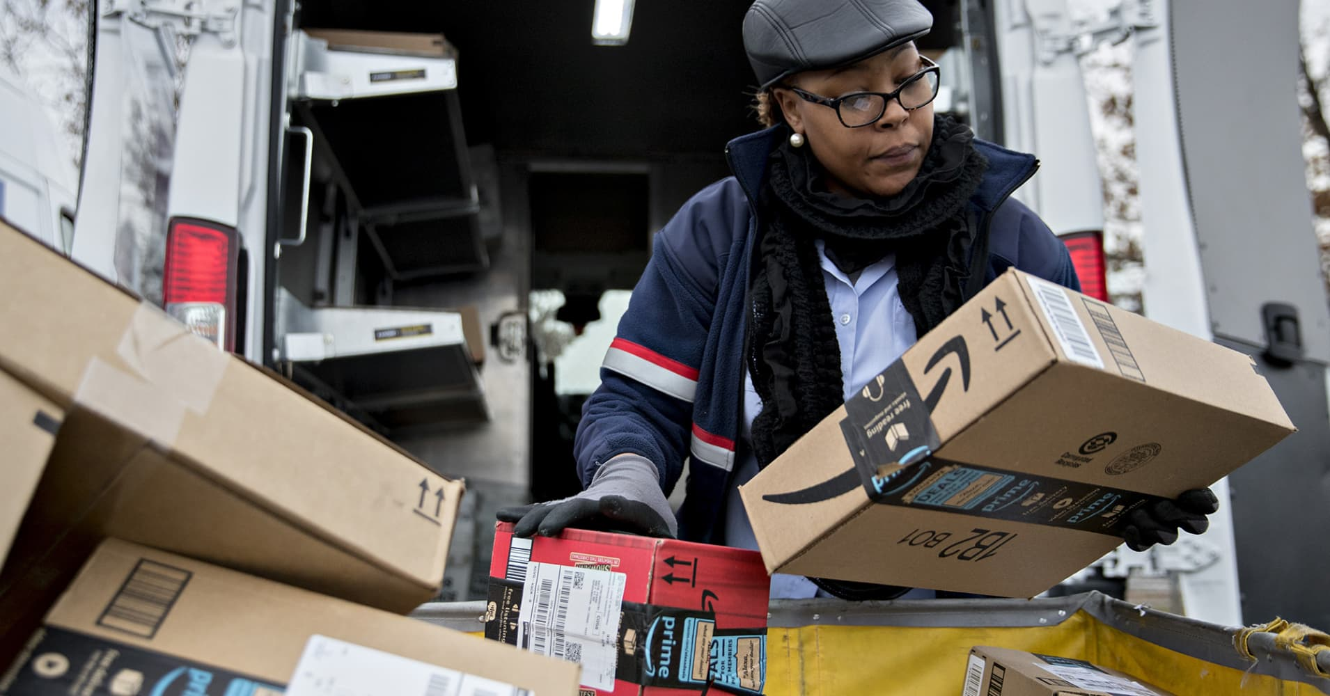 A letter carrier holds Amazon.com packages while preparing a vehicle for deliveries at a United States Postal Service processing and distribution center in Washington, D.C.