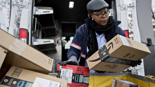 A letter carrier holds Amazon.com packages while preparing a vehicle for deliveries at the United States Postal Service (USPS) Joseph Curseen Jr. and Thomas Morris Jr. processing and distribution center in Washington, D.C.