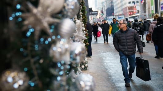 A man carrying a shopping bag walks past holiday decorations along Fifth Avenue in Midtown Manhattan.