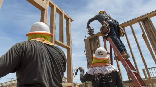 Contractors raise framed walls at the PulteGroup Onyx housing development in San Jose, California.
