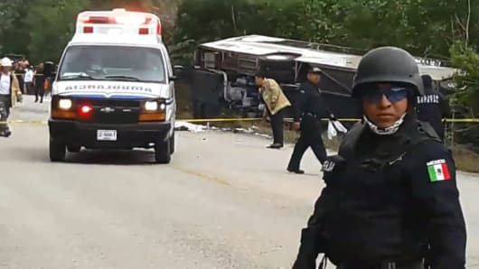 Video grab of Mexican police officers standing guard in the area where a bus driving tourists to Chacchoben archaeological zone overturned in the road in Mexico on December 19, 2017