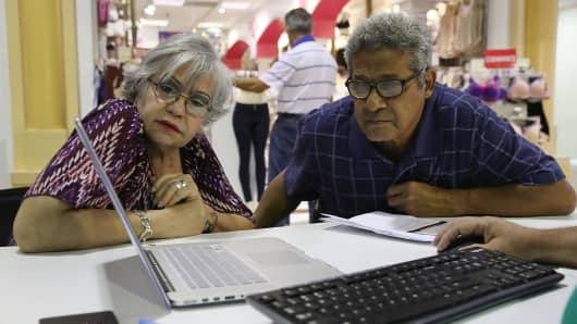 Isabel Diaz Tinoco (L) and Jose Luis Tinoco look at a computer as Otto Hernandez, an insurance agent from Sunshine Life and Health Advisors, shows them the different insurance plans available under the Affordable Care Act at a store setup in the Mall of Americas on November 1, 2017 in Miami, Florida.