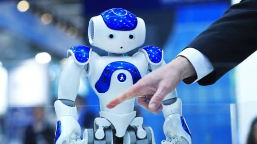 An arm gestures in front of a NAO humanoid robot, developed by Softbank Corp., at the CeBIT 2017 tech fair in Hannover, Germany last March.