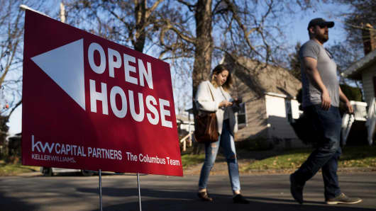 Potential home buyers walk past an 'Open House' sign displayed in the front yard of a property for sale in Columbus, Ohio.