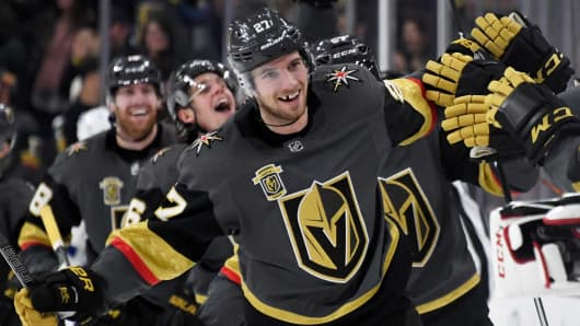 Shea Theodore #27 of the Vegas Golden Knights celebrates with teammates after scoring on a power-play goal with 2.3 seconds left in the third period to beat the Tampa Bay Lightning 4-3 at T-Mobile Arena on December 19, 2017 in Las Vegas, Nevada.