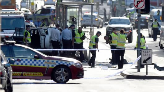 Police and emergency personnel work at the scene of where a car ran over pedestrians in Flinders Street in Melbourne on December 21, 2017. The car ploughed into a crowd in Australia's second-largest city on December 21, injuring at least a dozen people, some of them seriously, officials said.