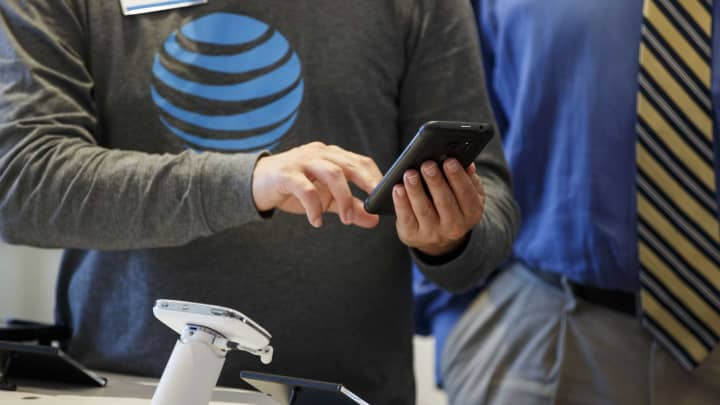 An employee helps a customer with a smartphone at an AT&T Inc. store in Newport Beach, California.