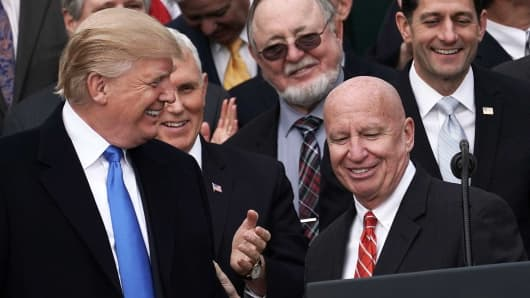 President Donald Trump (L) shares a moment with Chairman of House Ways and Means Committee Rep. Kevin Brady (R-TX) (4th L) as Vice President Mike Pence (2nd L), Rep. Don Young (R-AK) (3rd L) and Speaker of the House Rep. Paul Ryan (R-WI) (R) look on during an event to celebrate Congress passing the Tax Cuts and Jobs Act with Republican members of the House and Senate on the South Lawn of the White House December 20, 2017 in Washington, DC.