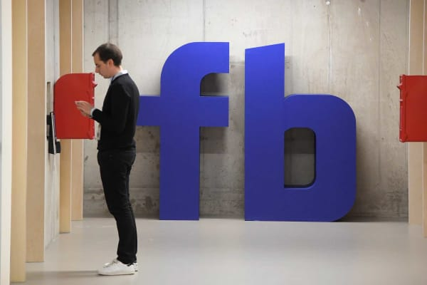 An employee waits for an elevator at a Facebook office.