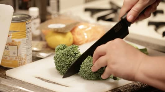 Chopping broccolini for meal from Purple Carrot