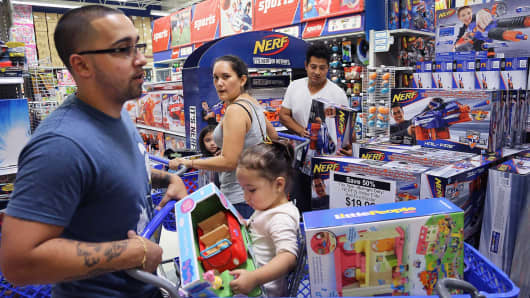 Johnathan Beauchamp, left, and daughter Alaya, 1, squeeze by fellow shoppers Diana Barrios, center, and husband Pablo Barrios, right, to shop at the 'Toys R Us' in Doral, Fla.