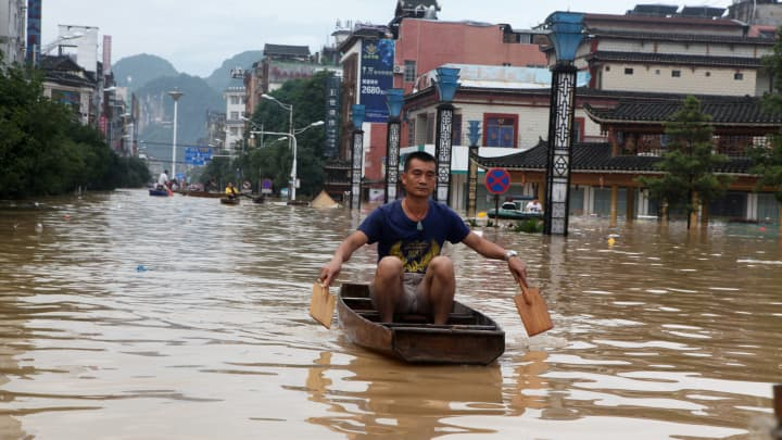 A man makes his way with a wooden boat through a flooded area in Liuzhou, Guangxi province, China July 2, 2017. Picture taken July 2, 2017.