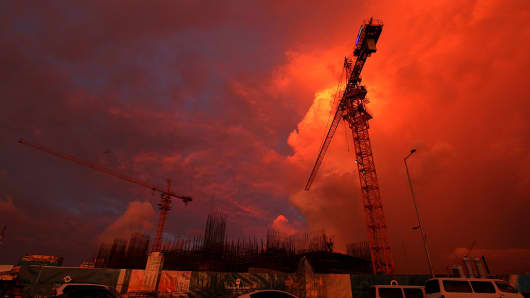 Cranes stand during the sunset at a construction site at the hotel complex construct by Chinese company on October 15, 2015 in Colombo, Sri Lanka.