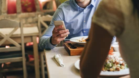 Man checking smartphone at dinner table
