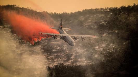 A California Air National Guard C-130J Hercules drops fire retardant over the hills above Santa Barbara, Calif., Dec. 13, 2017, while helping fight the Thomas Fire.