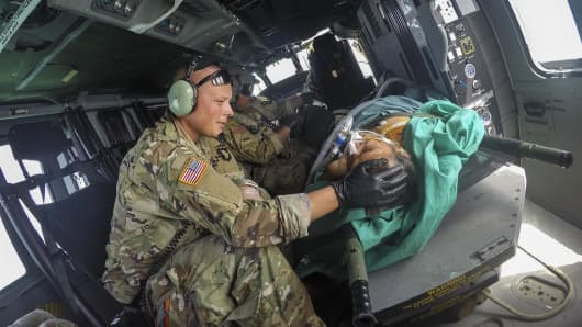 Army Capt. Benjamin Stork, a flight surgeon, cares for a patient on an HH-60 Blackhawk helicopter headed to the USNS Comfort, a hospital ship off the coast of Puerto Rico, Oct. 20, 2017, following Hurricane Maria.