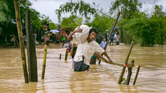 Refugees cross a flooded bridge in the Balukhali Rohingya refugee camp on September 19, 2017 in Cox's Bazar, Bangladesh.