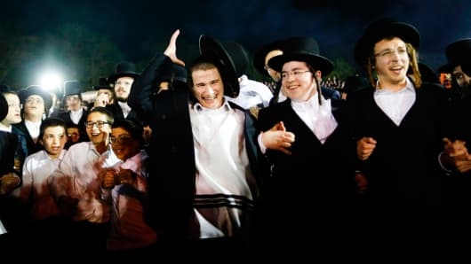 Orthodox Jews of the Satmar Hasidim dance in the village of Kiryas Joel, New York, May 14, 2017, during celebrations for the Jewish holiday of Lag BaOmer, marking the anniversary of the death of Talmudic sage Rabbi Shimon Bar Yochai approximately 1,900 yea