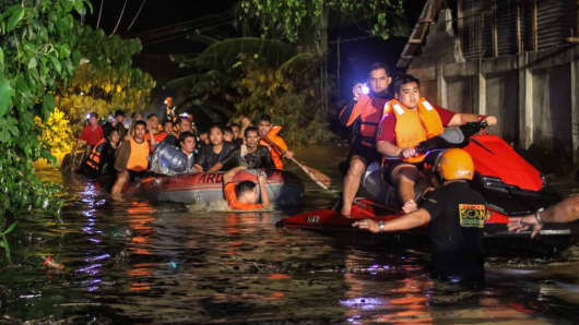 Rescue workers evacuate flood-affected residents in Davao on the southern Philippine island of Mindanao early on December 23, 2017, after Tropical Storm Tembin dumped torrential rains across the island.
