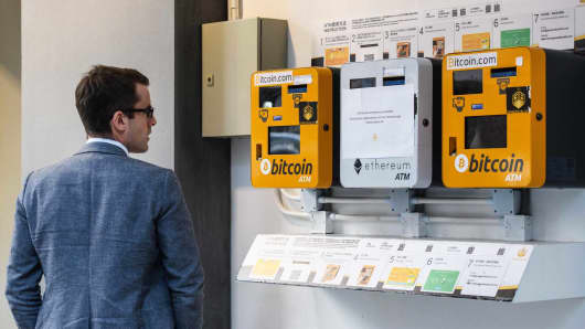 A man looks at ATM machines for digital currency Bitcoin in Hong Kong.