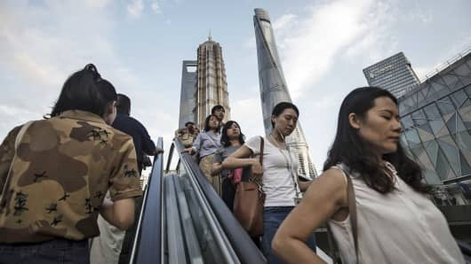Pedestrians ride an escalator near the Jin Mao Tower, center left, and the Shanghai Tower, center right, in the Lujiazui Financial District in Shanghai, China.