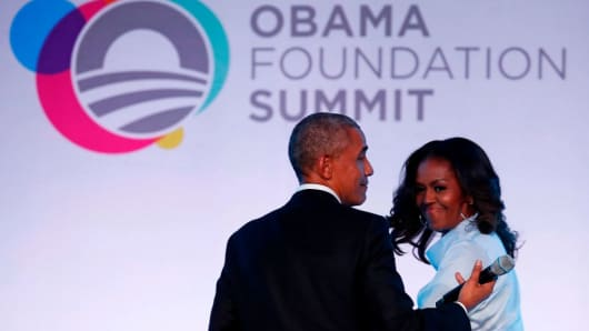 Former US president Barack Obama and his wife Michelle walk off the stage at the Obama Foundation Summit in Chicago, Illinois, October 31, 2017.