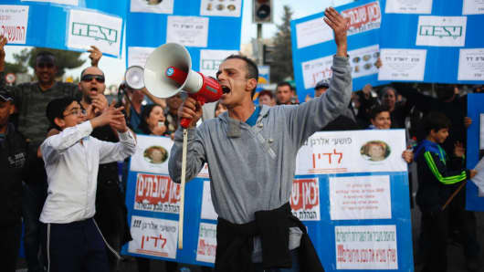 Workers protest outside the Teva Pharmaceutical Industries factory as the block a main road in Jerusalem, Sunday, Dec. 17, 2017.