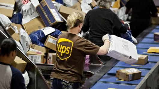 Employees sort packages at the United Parcel Service (UPS) Chicago Area Consolidation Hub in Hodgkins, Illinois.