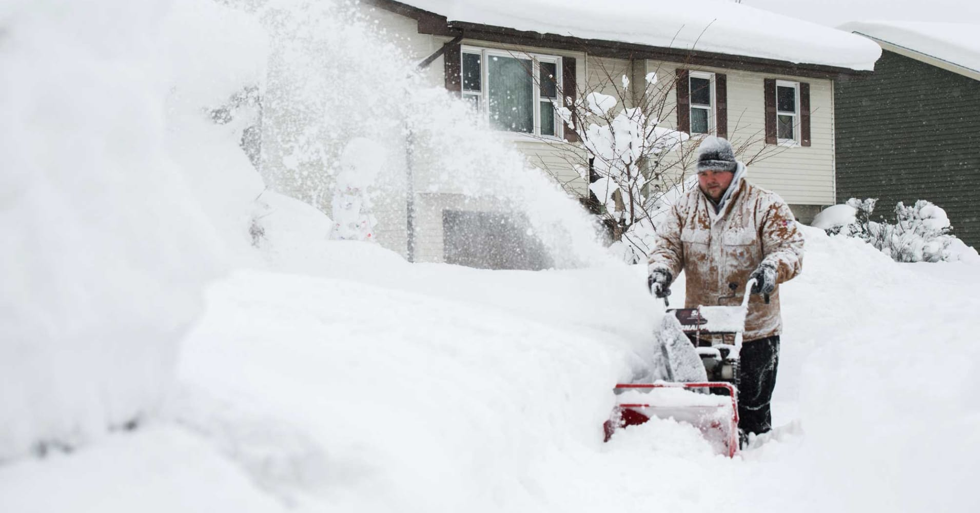 Thomas Berry removes snow from the sidewalk in front of his home after two days of record-breaking snowfall in Erie, Pennsylvania, December 27, 2017.