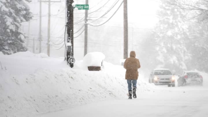 A resident walks north on Pine Ave as more snow falls after two days of record-breaking snowfall in Erie, Pennsylvania, December 27, 2017.