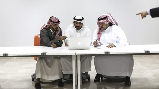 A group of Saudi business students use an Apple Inc. laptop computer
