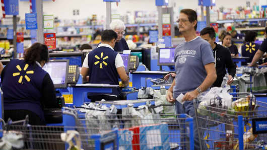Cashiers ring up customers at registers inside a Walmart location in Burbank, California.
