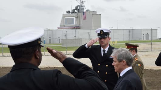 Romanian Prime Minister Dacian Ciolos (C) looks on as US Army servicemen salute during the inauguration ceremony of the Aegis Ashore Romania facility at the Deveselu military base on May 12, 2016.