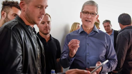 Tim Cook, chief executive officer of Apple Inc., right, speaks with Ryan Tedder, lead singer of One Republic, as other members of the band look on after a product announcement in San Francisco, Sept. 9, 2015.  Apple is expected to unveil its iPhone 6s and 6s Plus.