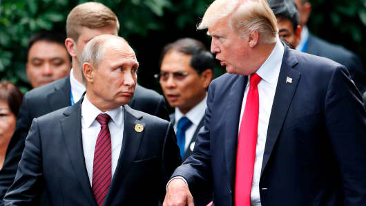 US President Donald Trump (R) and Russia's President Vladimir Putin talk as they make their way to take the 'family photo' during the Asia-Pacific Economic Cooperation (APEC) leaders' summit in the central Vietnamese city of Danang on November 11, 2017.