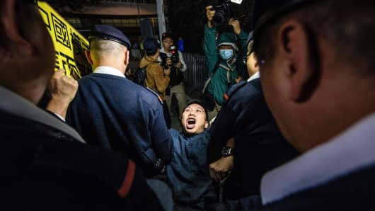 One of the last protesters is removed by members of security as he takes part in a New Year's Day pro-democracy rally in Hong Kong at the recently reopened Civic Square late on January 1, 2018.