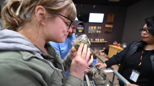 A tourist visiting from Arizona, smells cannabis buds at the Green Pearl Organics dispensary on the first day of legal recreational marijuana sales in California, January, 1, 2018 in Desert Hot Springs.