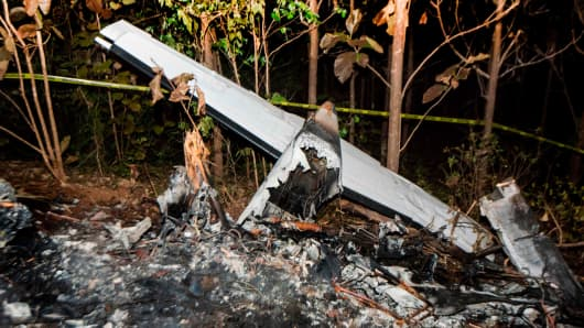 The tail of the burned fuselage of a small plane that crashed, rests near trees in Guanacaste, Corozalito, Costa Rica on December 31, 2017.