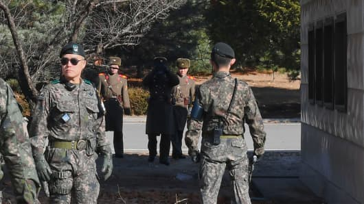 North Korean soldiers stare at South Korean soldiers at the truce village of Panmunjom in the Demilitarized zone (DMZ) dividing the two Koreas on November 27, 2017.