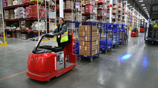 A worker pulls carts full of customer orders along the floor inside the million-square foot Amazon distribution warehouse that opened last fall in Fall River, MA.
