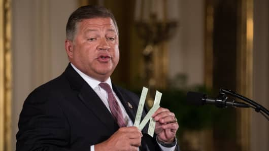 Rep. Bill Shuster (R-PA), Chairman, House T&I Committee, holds up strips of paper air traffic controllers currently use, as he speaks at President Donald Trump's event announcing the Air Traffic Control Reform Initiative in the East Room of the White House, on Monday, June 5, 2017.