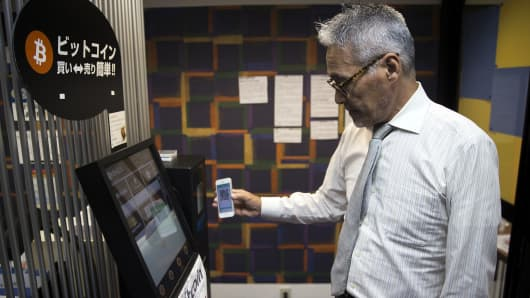 A Coin Trader employee uses a smartphone to demonstrates how to purchase bitcoins from an automated teller machine in Tokyo.