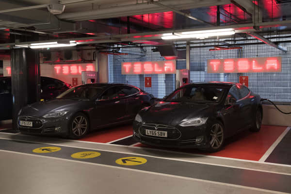 Tesla electric cars are charged at a Tesla Supercharger station, in Westfields shopping centre in west London on December 19, 2107.