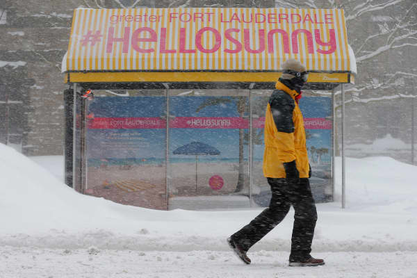 A pedestrian walks past a bus stop with an advertisement for Florida during a winter blizzard in Boston, Massachusetts.