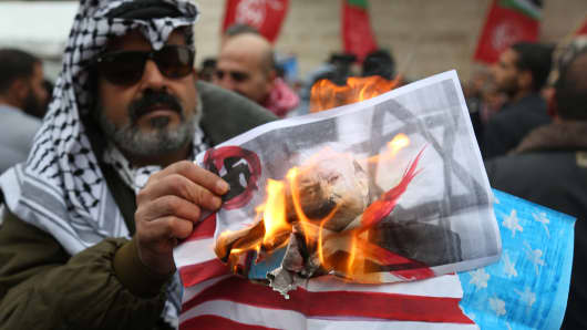 Palestinians burn posters depicting U.S. President Donald Trump and a U.S. flag and Israeli flag during a protest against Trump's decision to recognize Jerusalem as the capital of Israel, in Gaza City on January 1, 2018.