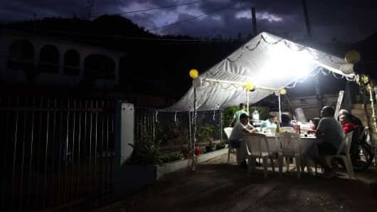 Residents of the El Salto neighbourhood share a meal during New Year's Eve after Hurricane Maria damaged the electrical grid in September, in Morovis, Puerto Rico December 31, 2017. Picture taken December 31, 2017.